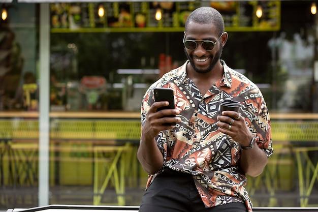 Bel homme avec des lunettes de soleil à l'aide d'un smartphone à l'extérieur tout en prenant un café