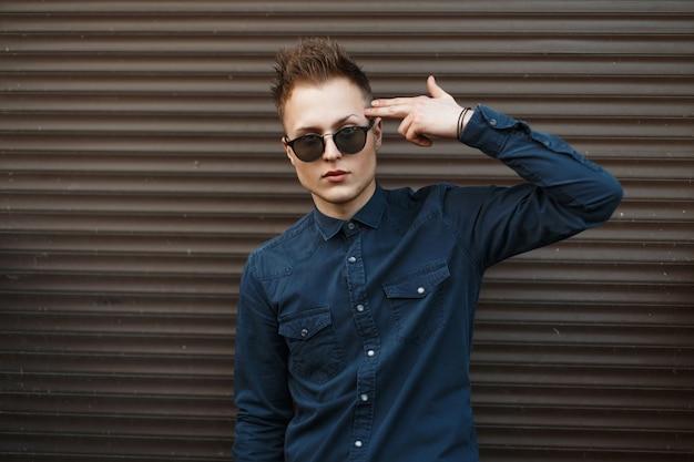 Bel homme à lunettes de soleil à la mode posant près de mur métallique