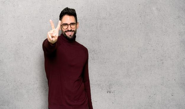 Bel homme avec des lunettes en souriant et en montrant le signe de la victoire sur le mur texturé