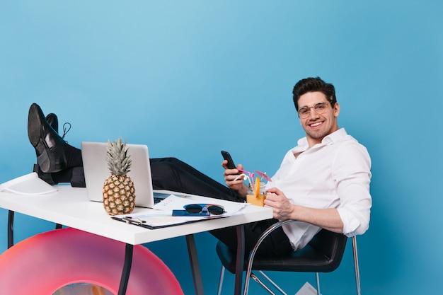 Bel homme à lunettes et tenue de bureau regarde la caméra avec le sourire, tient le smartphone, apprécie le cocktail et s'assoit à table avec ordinateur portable, cercle gonflable et ananas.