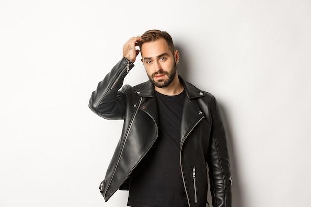 Bel homme macho en veste de motard noir, touchant sa coupe de cheveux et à la cool