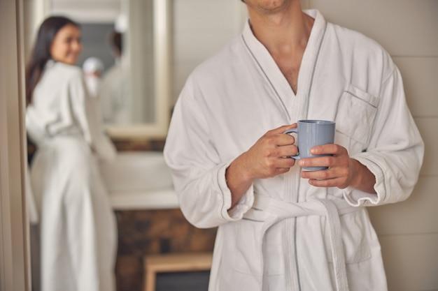 Bel homme main tenant une tasse de thé dans la salle de bain