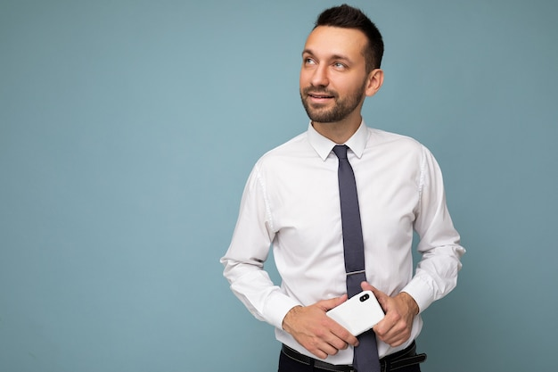 Bel homme mal rasé brunet réfléchi avec barbe portant une chemise et une cravate blanches décontractées