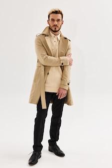Bel homme en manteau de mode automne style studio fond clair. photo de haute qualité