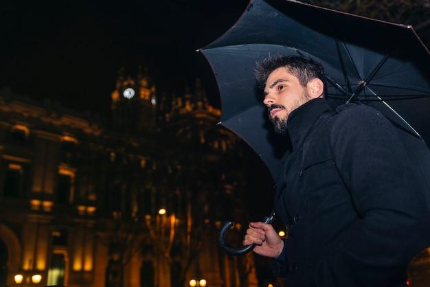 Bel homme marchant à madrid la nuit sous la pluie.