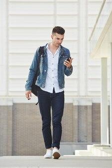 Bel homme marchant avec un téléphone portable et des écouteurs à l'extérieur