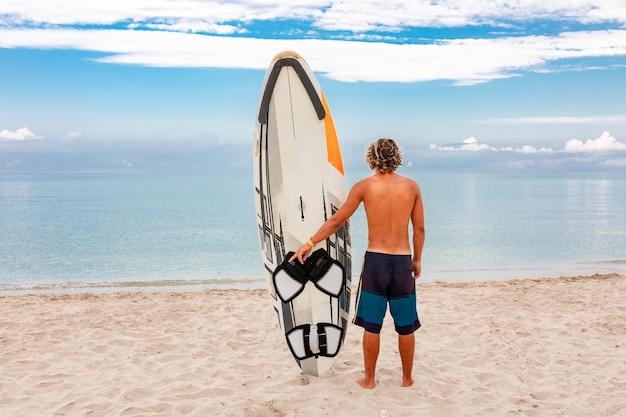 Bel homme marcher avec planche de surf blanc blanc attendre la vague pour surfer sur place au bord de mer océan. concept de sport, fitness, liberté, bonheur, nouvelle vie moderne, hipster.