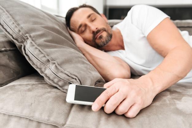 Bel homme mature dormant sur un canapé