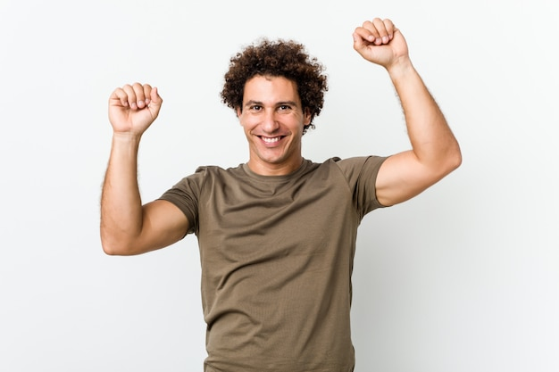 Bel homme mature isolé célébrant une journée spéciale, saute et lève les bras avec énergie.