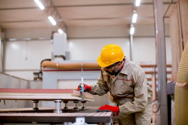 Bel homme mature travaillant dans une usine de meubles