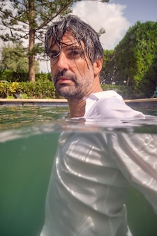 Bel homme mature en vêtements mouillés dans la piscine