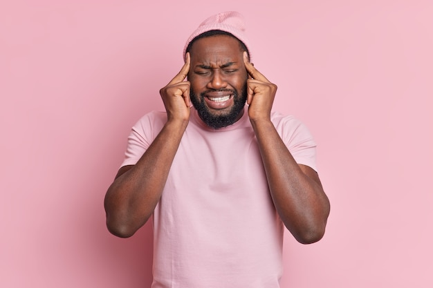 Bel homme mécontent avec une barbe épaisse souffre d'une migraine insupportable garde les doigts sur les tempes pour révéler la douleur serre les dents porte un t-shirt décontracté et un chapeau pose sur un mur rose pâle