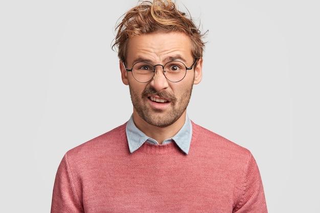 Bel homme mécontent fronce les sourcils avec mécontentement, ressent de l'aversion en remarquant quelque chose de dégoûtant, a une coiffure à la mode