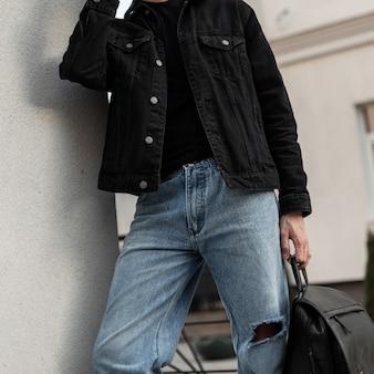 Bel homme à la mode dans une chemise en jean noir avec un t-shirt noir et un jean classique bleu tient un sac à dos en cuir noir dans la rue