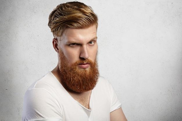 Bel homme à la mode avec une longue barbe rouge et une coiffure à la mode ayant une expression faciale sérieuse et mécontente renfrognée et fronçant les sourcils en se tenant debout contre un mur de béton