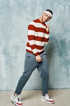 Bel homme en mode pull rayé posant un studio de style moderne