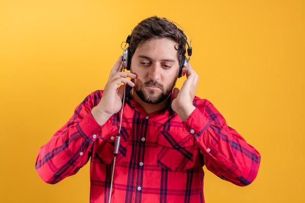 Bel homme moderne, écouter de la musique dans des écouteurs sur jaune
