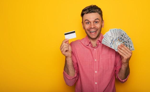 Un bel homme moderne et prospère montre une carte de crédit et beaucoup d'argent sur l'appareil photo pour faire des achats en ligne