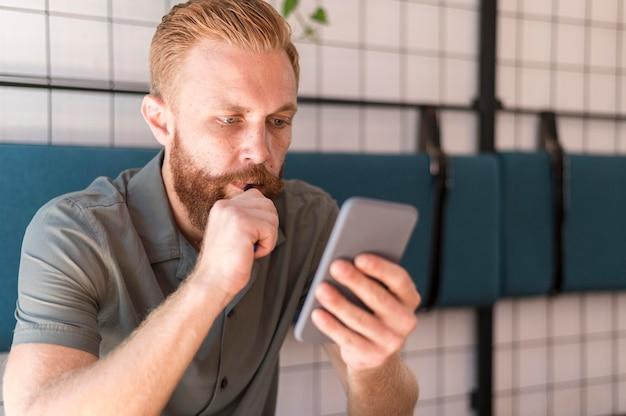 Bel homme moderne en regardant son téléphone