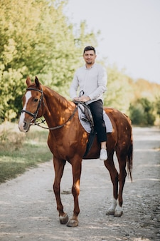 Bel homme monté sur un cheval en forêt