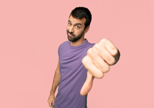 Bel homme montrant le pouce vers le bas de signe avec une expression négative sur fond rose isolé