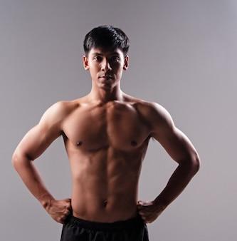 Le bel homme montre le muscle du corps