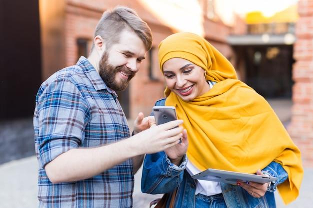 Bel homme montre une photo sur smartphone à une jeune femme arabe