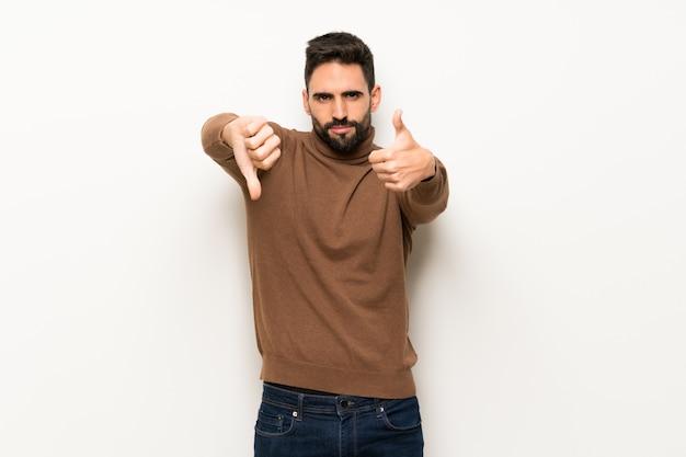 Bel homme sur un mur blanc faisant bon signe. indécis entre oui ou non