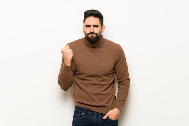 Bel homme sur un mur blanc avec un geste de colère