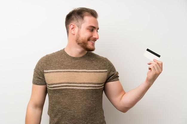 Bel homme sur mur blanc isolé, tenant une carte de crédit