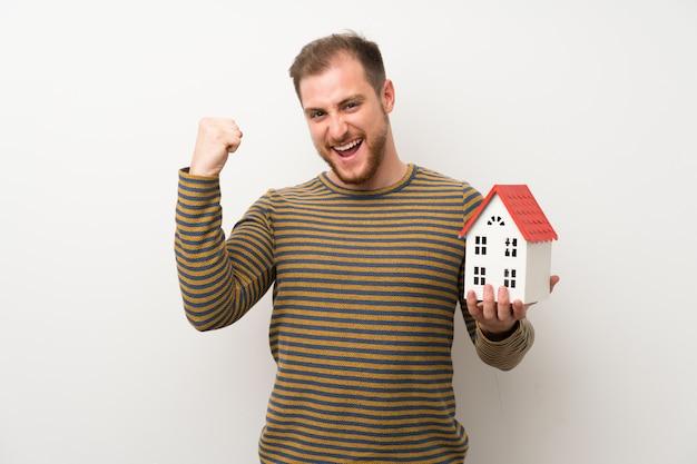 Bel homme sur un mur blanc isolé, tenant une petite maison