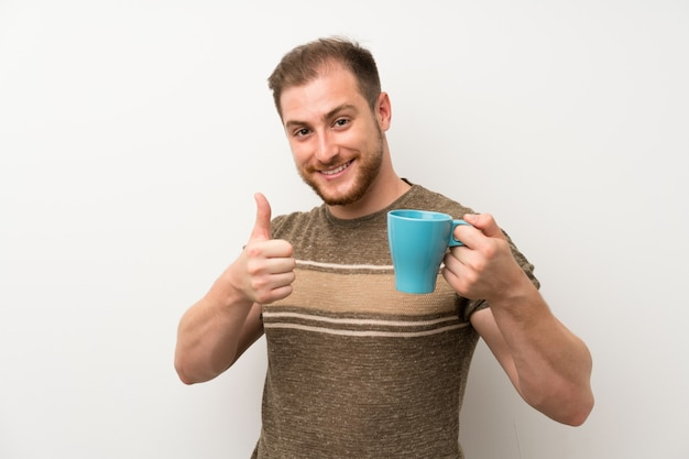 Bel homme sur un mur blanc isolé, tenant une tasse de café