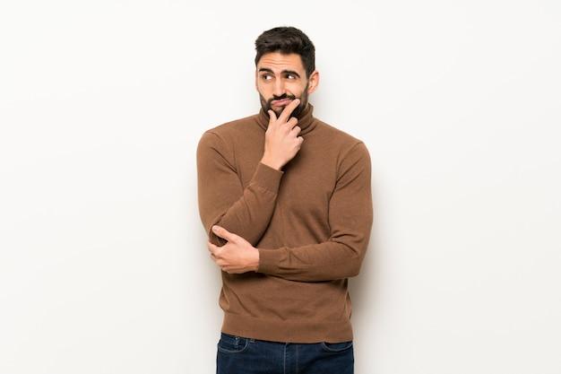 Bel homme sur mur blanc souriant et regardant vers l'avant avec un visage confiant