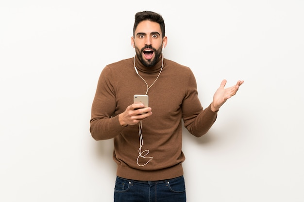 Bel homme sur un mur blanc surpris et envoyant un message
