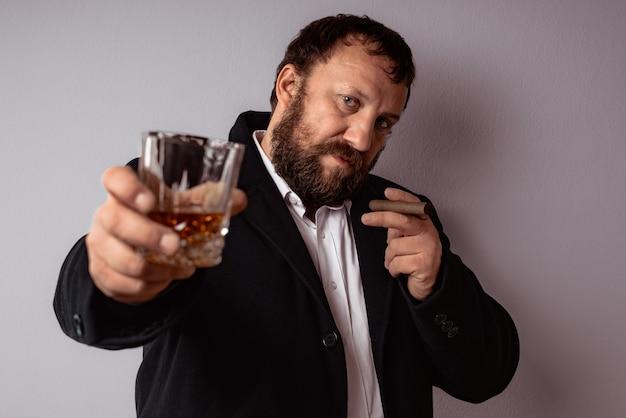 Bel homme mûr confiant avec barbe boire de l'alcool fort et fumer son cigare