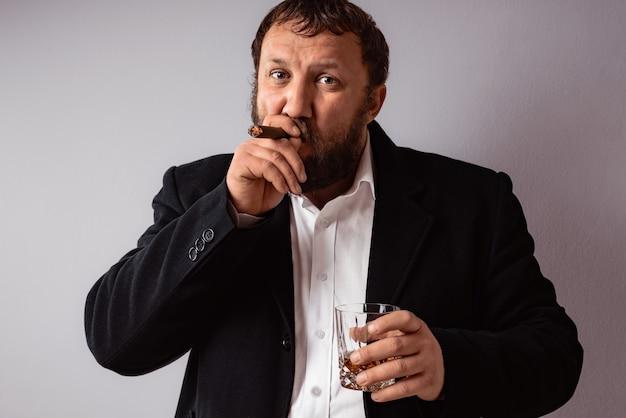 Bel homme mûr confiant avec barbe qui porte un manteau et une chemise fumant son cigare à la célébration