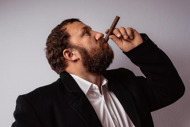 Bel homme mûr confiant avec barbe qui porte manteau et chemise fumant son cigare