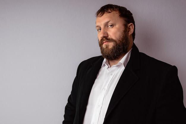 Bel homme mûr confiant avec barbe qui porte manteau et chemise se dresse sur fond gris.