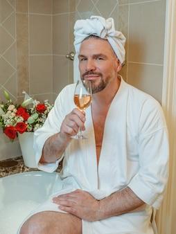 Bel homme mûr gay en peignoir blanc et serviette sur la tête assis sur la salle de bain avec de la mousse