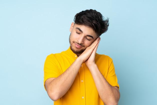 Bel homme sur un mur isolé faisant un geste de sommeil dans une expression adorable