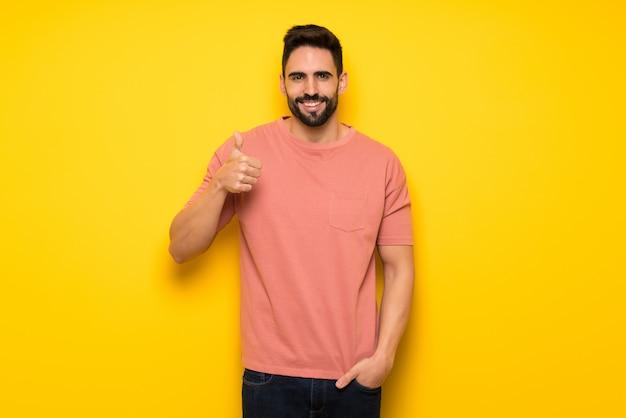 Bel homme sur mur jaune donnant un geste du pouce avec les deux mains et souriant