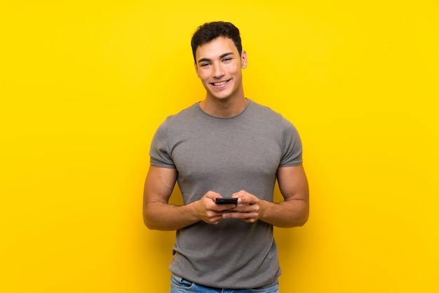 Bel homme sur un mur jaune isolé, envoyant un message avec le téléphone portable
