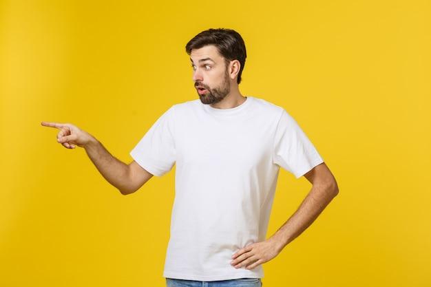 Bel homme sur un mur jaune isolé frustré et pointant vers l'avant