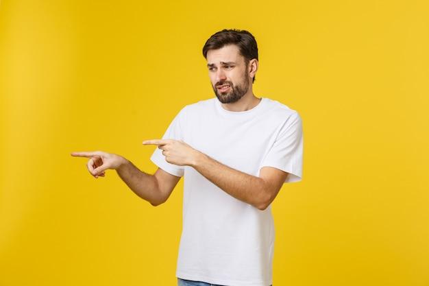 Bel homme sur mur jaune isolé frustré et pointant vers l'avant.
