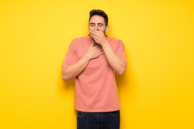 Bel homme sur un mur jaune souffre de toux et se sent mal