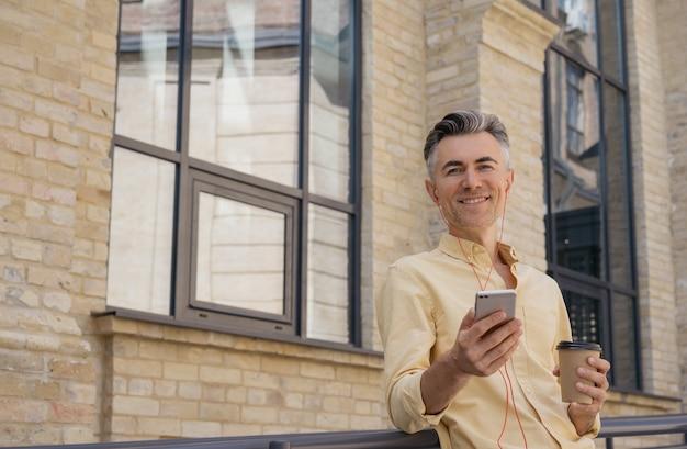 Bel homme mûr tenant un téléphone mobile