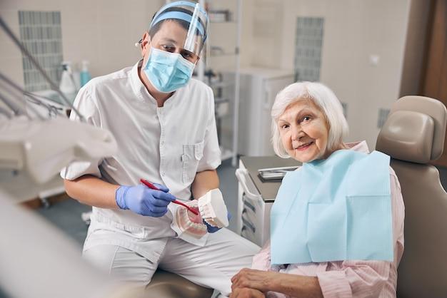 Bel homme mûr en uniforme blanc tenant un modèle de mâchoire de dents lors d'une démonstration de nettoyage dentaire avec une brosse à dents