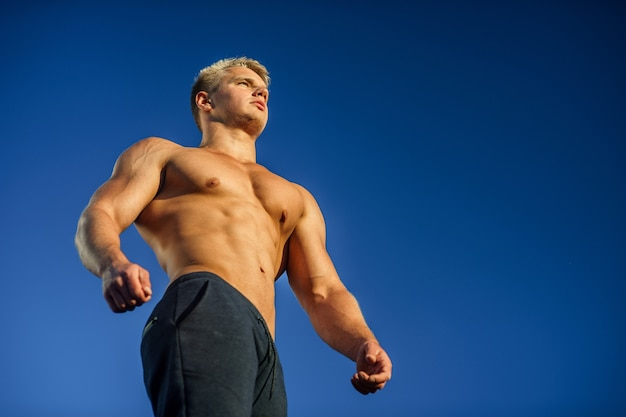Bel homme musclé posant avec un ciel bleu