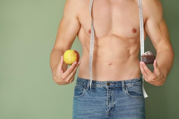 Bel homme musclé avec ruban à mesurer, dessert et pomme sur la couleur.