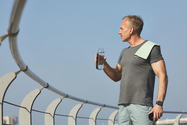 Bel homme musclé avec une serviette sur l'épaule en contemplant la rivière tout en buvant de l'eau après l'entraînement